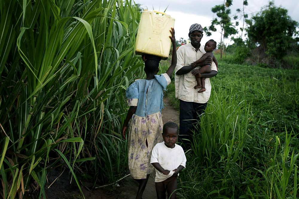 Gladys Aromo, age 12, carries a container with drinking water while walking to her house n Lailiya, Uganda, 2005. Gladys is a night commuter, one of about 20,000 children that sleep in Gulu town, as they are afraid of being abducted by the Lord's Resistance Army (LRA). The rebel group has brought terror to Northern Uganda for almost twenty years, fighting the Ugandan government. The victims are usually children, which are abducted and used as child soldiers and sex slaves. Gladys walks 1,5 hour from her home every day to sleep at Noah's Arch, an NGO housing children in Gulu. She is too afraid to sleep in the village as an older sister was earlier abducted. She walks a further 30 minutes every day to attend school.