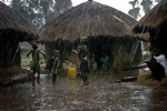 Children play outside huts in a heavy rainfall in Laliya, a poor rural village in northern Uganda, 2005. Many children in this area are afraid of being abducted by the Lord's Resistance Army (LRA). The rebel group has brought terror to Northern Uganda for almost twenty years, fighting the Ugandan government. The victims are usually children, which are abducted and used as child soldiers and sex slaves.