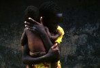 Susan Labol, age 10, hugs her little sister outside her family's hut in Laliya, a rural village in Northern Uganda, 2005. Susan is a night commuter, one of about 20,000 children that sleep in Gulu town, as they are afraid of being abducted by the Lord's Resistance Army (LRA). The rebel group has brought terror to Northern Uganda for almost twenty years, fighting the Ugandan government. The victims are usually children, which are abducted and used as child soldiers and sex slaves. Susan walks 1.5 hours from her home village with her sister Gladys, age 12, every day to sleep at Noah's Arch, an NGO housing children in Gulu. They are too afraid to sleep in the village as an older sister was earlier abducted.