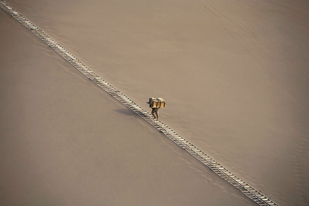 A man carries wooden slides along a path in the desert dunes in Gobi desert, DunHuang, China, 2007