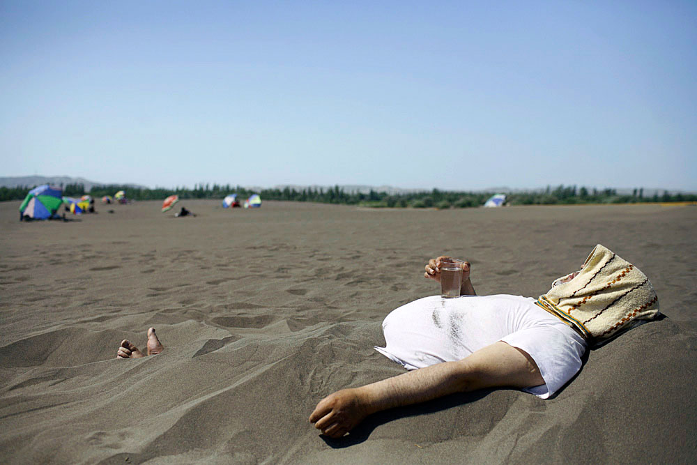 An ethnic Uygur man drinks tea while resting in hot sand at a Sand Therapy Center, Turpan, China, 2007