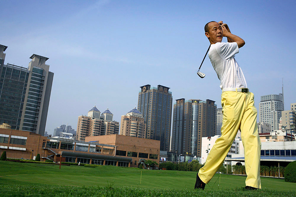 Zhang Yi, age 44, a director for an insurance company with 200 employees, plays golf at the Xian Country Club, Xian, China, 2007