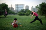 A woman works out in a park as her daughter plays nearby in central Xian, China, 2007