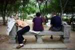 A man has fallen asleep on a bench after reading a newspaper in a park in central Xian, China, 2007