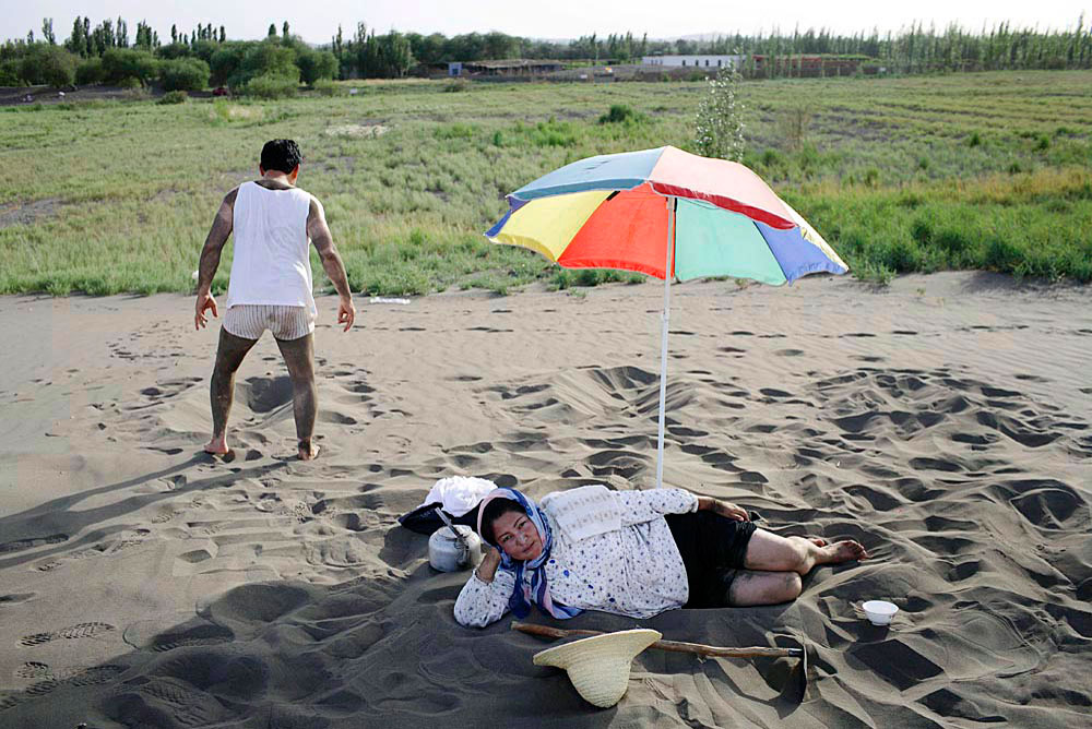 A Uygur woman rests in the sand as her husband takes a break from therapy at a sand therapy center, Turpan, China, 2007. An important part of Uygur traditional medicine.