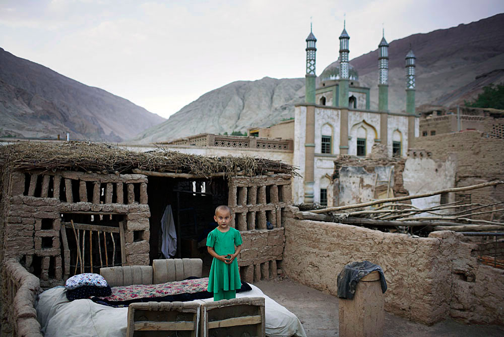 A young girl stands on the roof of the family house in an ancient village, Tuyoq, China, 2007
