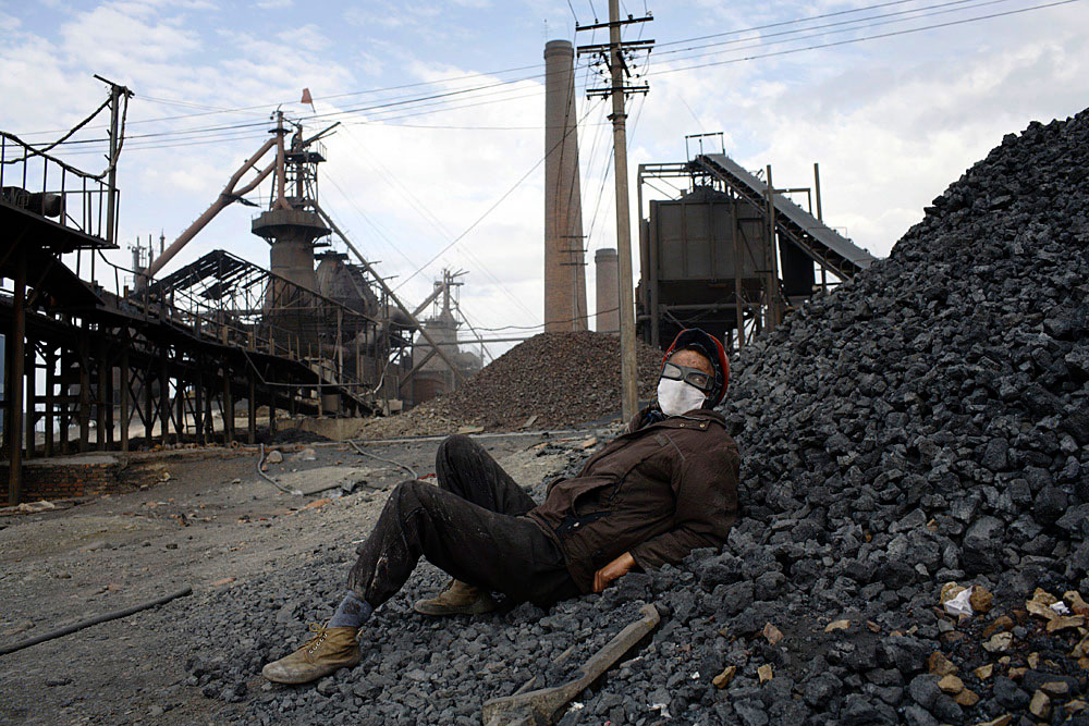 A worker rests on a pile of coal in a steel factory outside Turpan, China, 2007