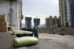 A migrant worker rests next to a new exclusive residential building in central Lanzhou, China, 2007
