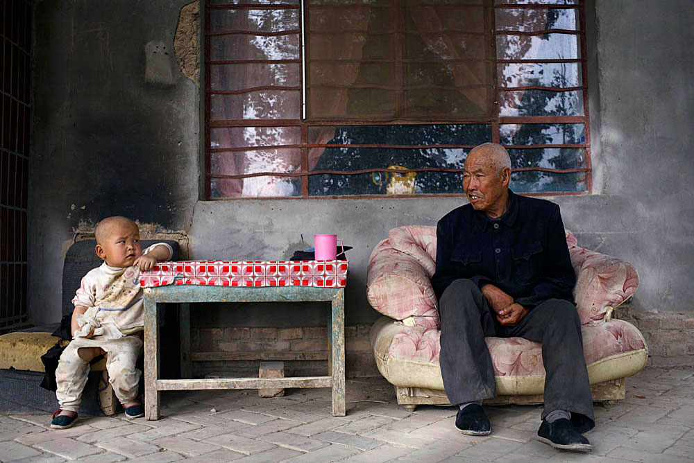An elderly man sits outside his house with his grandson in a small farming village outside DunHuang, China, 2007