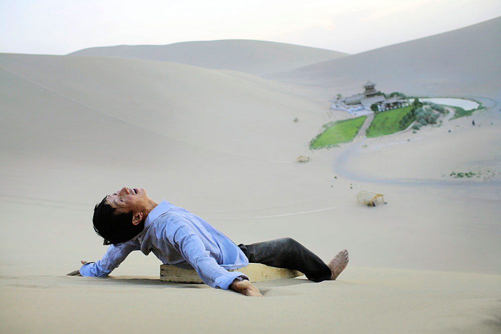 A man rides on a wooden slide in the desert dunes in Gobi desert, DunHuang, China, 2007