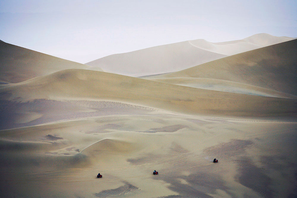 Chinese tourists ride on Quad bikes along the desert dunes in the Gobi desert outside DunHuang, China, 2007