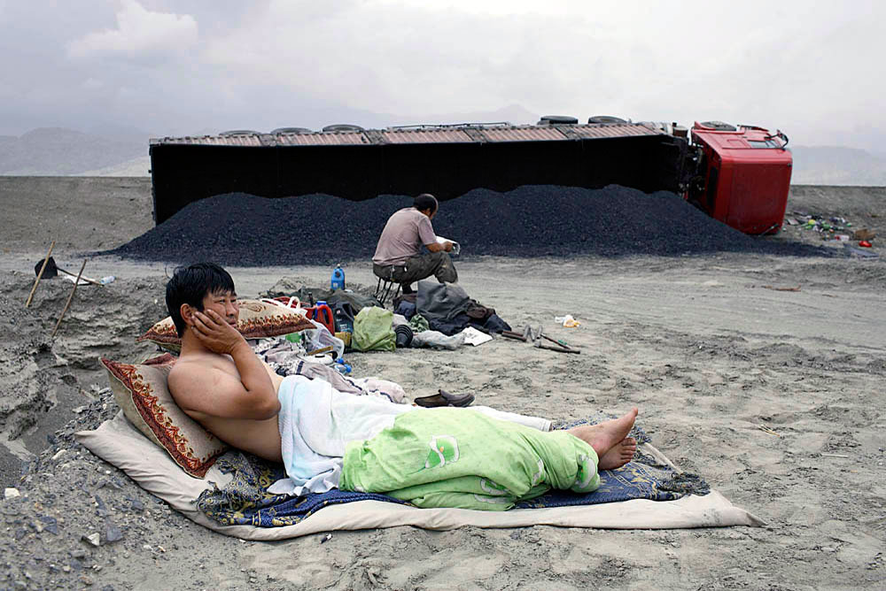 Shuidong Lxuidon, age 42, a truck diver, lays on the ground next to his truck outside Kurle, China, 2007. He drove straight for about 26 hours and fell asleep and drove off the road.