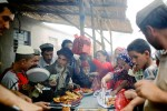 Ethnic Uygur villagers buy food from a stall at a weekly market, Khotan, China, 2007. Thousands of villagers attend every week dressed in traditional clothing.