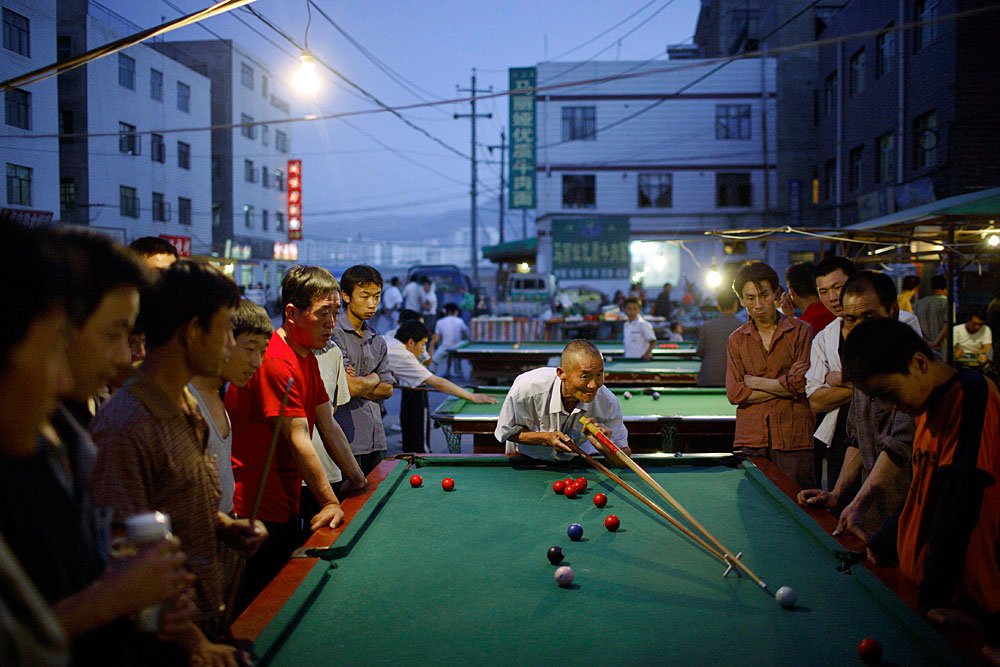 Migrant workers play pool at dusk in central Lanzhou, China, 2007