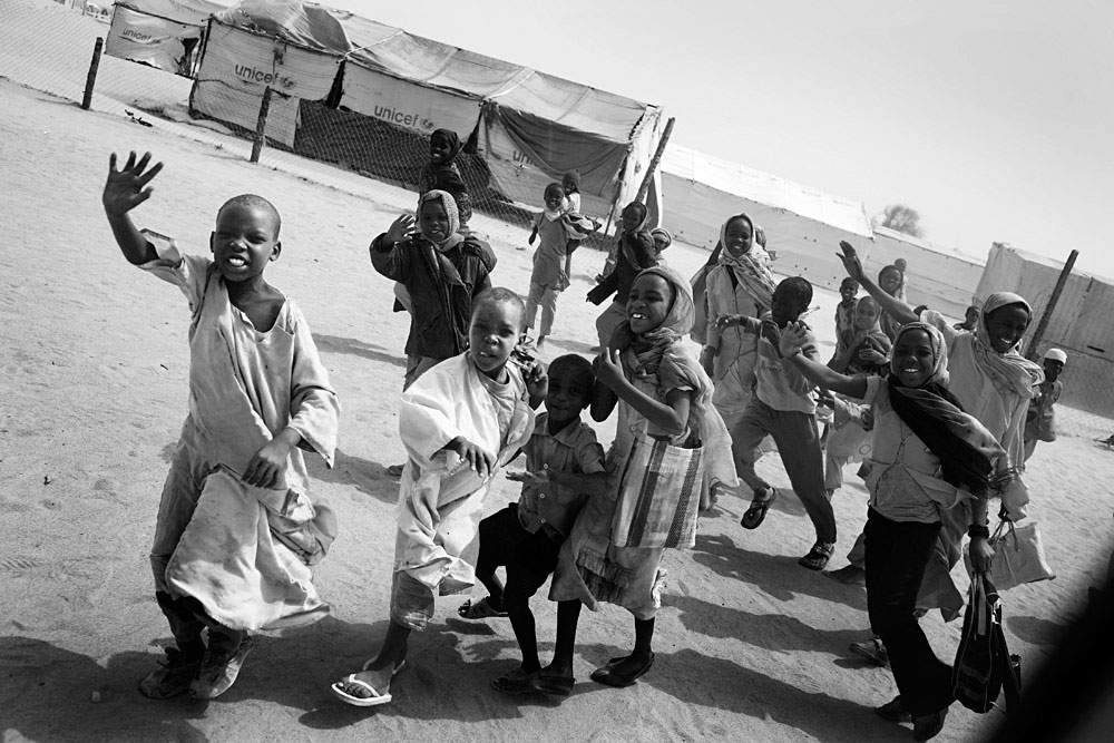 Refugee children greet aid workers in Oure Cassoni refugee camp close the border of Darfur, about 23 kilometers outside Bahai, Chad, 2007. About 26,000 people live in grim conditions after fleeing the violence in Darfur.