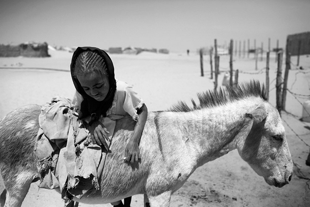 A refugee girl climbs a donkey after fetching water in the Oure Cassoni refugee camp close the border of Darfur, about 23 kilometers outside Bahai, Chad, 2007. About 27,000 people live in grim conditions after fleeing the violence in nearby Darfur.