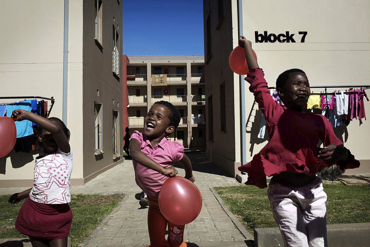 Children play outside the apartment block where they live on May 4, 2013 in Jabulani, section of Soweto, South Africa. Jabulani flats is one of the first apartment building developments in Soweto and local residents are just beginning learn how to live in an apartment. The residents of Soweto has seen massive investment such as shopping malls, parks, outdoor gyms in the township. (Photo by: Per-Anders Pettersson)