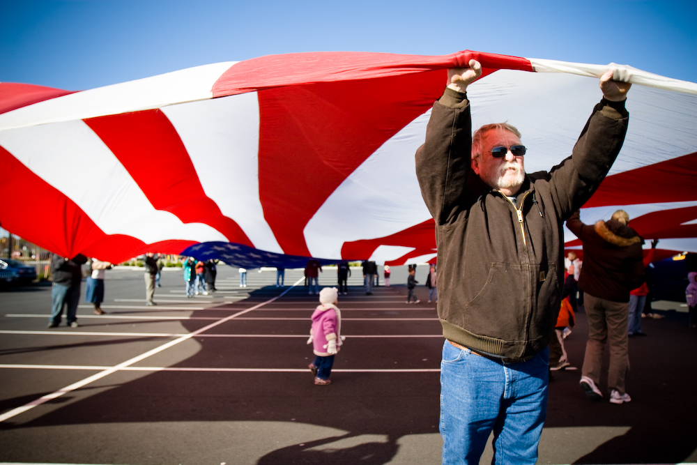 Volunteers salute veterans by unfurling a giant American flag at a flag appreciation ceremony.