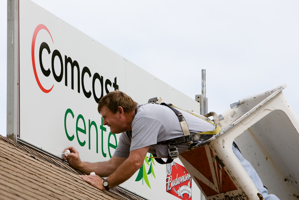 A worker paints the screwheards on a new sign after the renaming of the Tweeter Center to the Comcast Center.