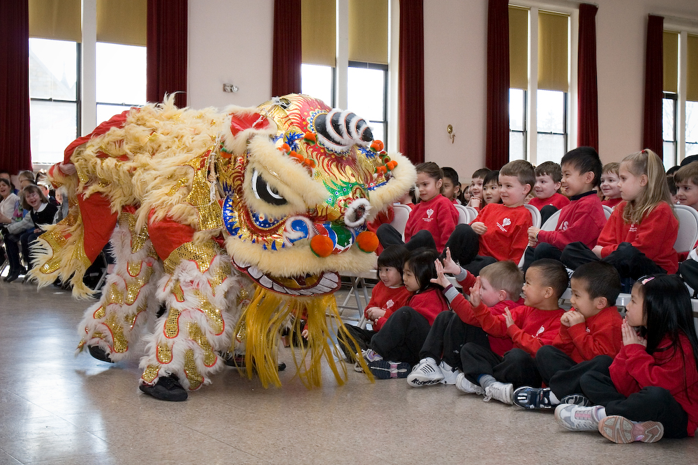Students at Sacred Heart School watch a lion dance performance as part of Chinese New Year festivities.