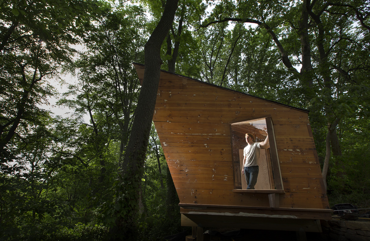 Jonathan Malloy with the cabin that he built  using recycled materials.