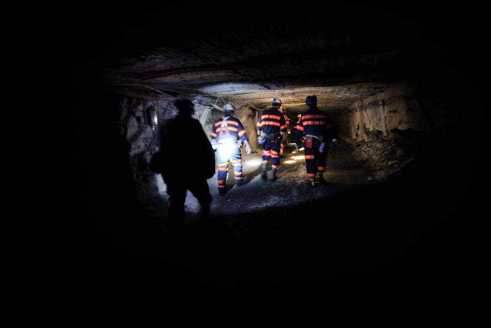 Coal miners illuminate their way with head lamps as they walk the long passage ways of the Cumberland mine in Waynesburg, Pa.