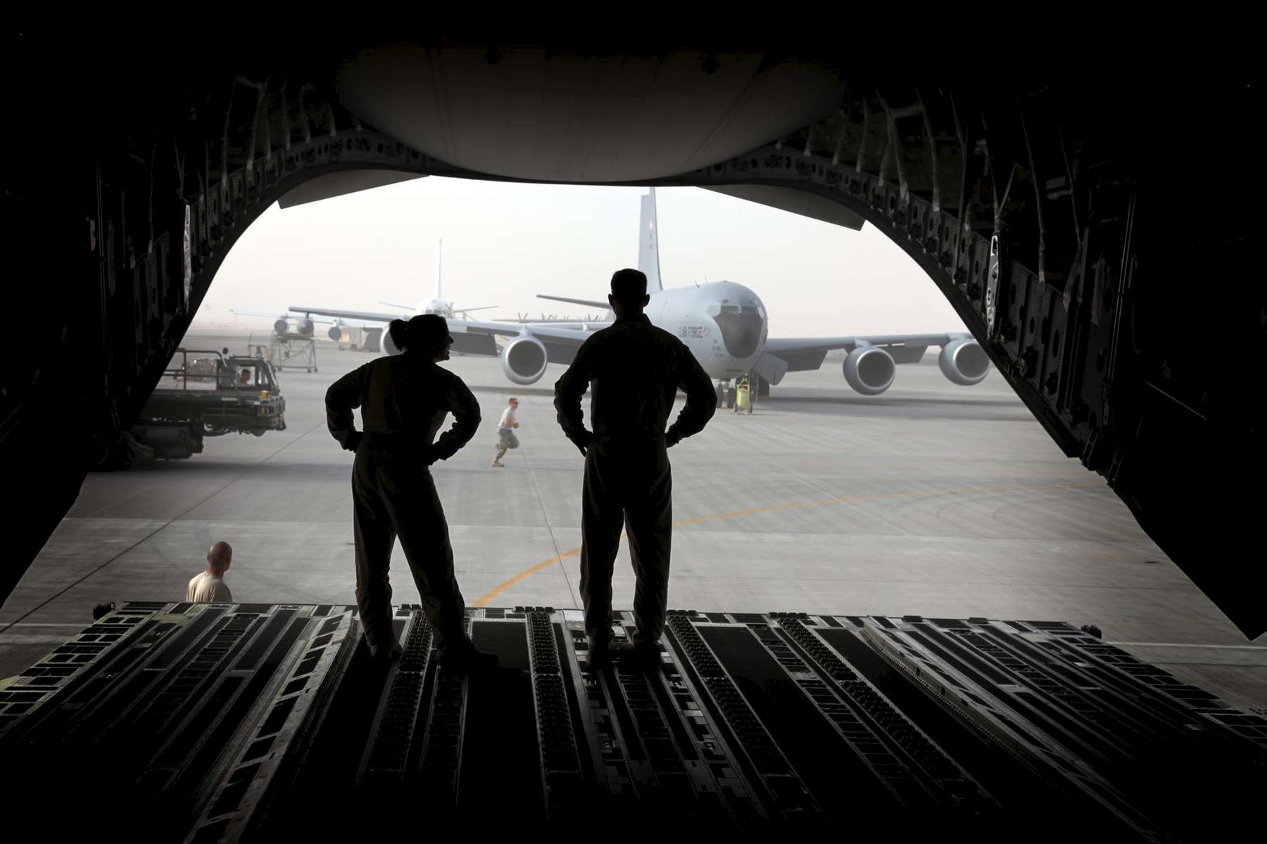 Loadmasters Senior Airman Christine Condoleon, left, and Master Sergeant Brian Cook, right,  stand on the loading ramp of their C17 cargo jet as they prepare to unload at an air base at an undisclosed location in the Persian Gulfon Saturday, February 23, 2009.  (Laurence Kesterson / Staff Photographer)  EDITORS NOTE:  JSUPPLY29, 2/21/09, McGuire AFB, New Jersey.  A supply mission to Afghanistan and other points in the Persian Gulf.