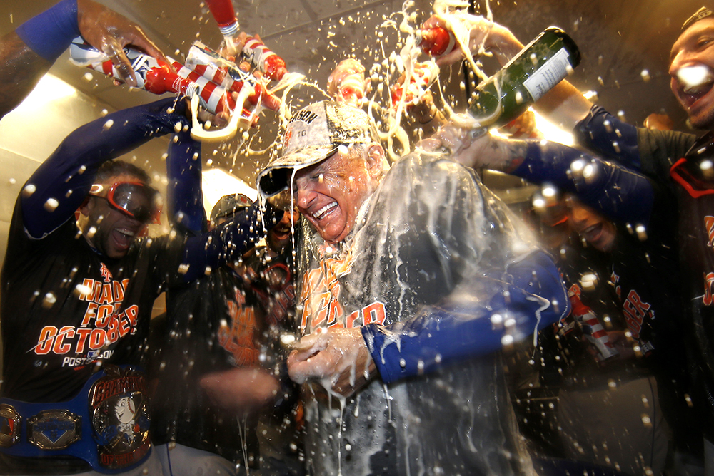 New York Mets manager Terry Colllins is sprayed with champaign and beer after the Mets secured a playoff position defeating the Philadelphia Phillies 5-3 in a baseball game, Saturday, Oct. 1, 2016, in Philadelphia. (AP Photo/Laurence Kesterson)