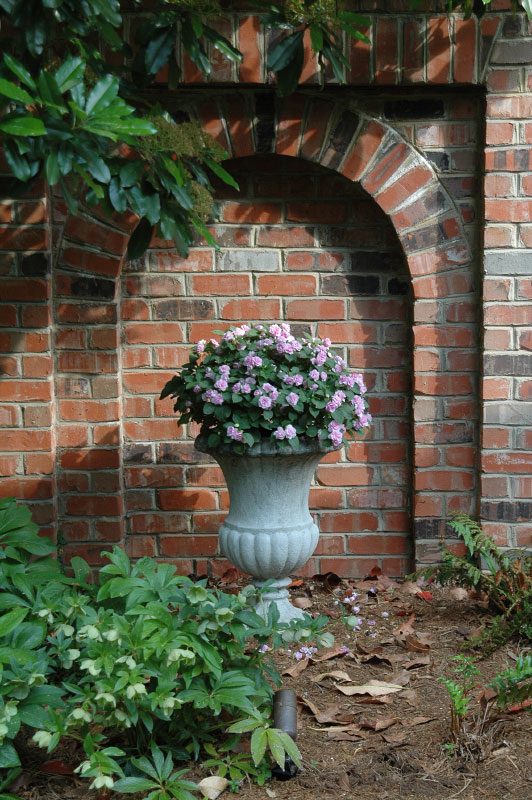 The arched niche is a focal point aloing the backyard crushed path and seperates the home from the neighboring property. This stone urn, filled with seasonal flora, helps soften the brick wall in the backdrop.