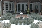 The rear courtyard becomes the center of attention from the home's rear windows. Now blanketed in snow, the circular placement of the evergreens appear to stand guard over the outdoor fountain.