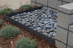 This area becomes a place to position an ornamental pot atop the beach pebbles.The edging surround features Cor-ten steel which will age to a sepia patina over time.