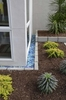 Blue glass block adds interest to the parallel lines of the home's charcoal gray concrete siding. The block sits in a bed built from the same aggregate block used throughout the design...