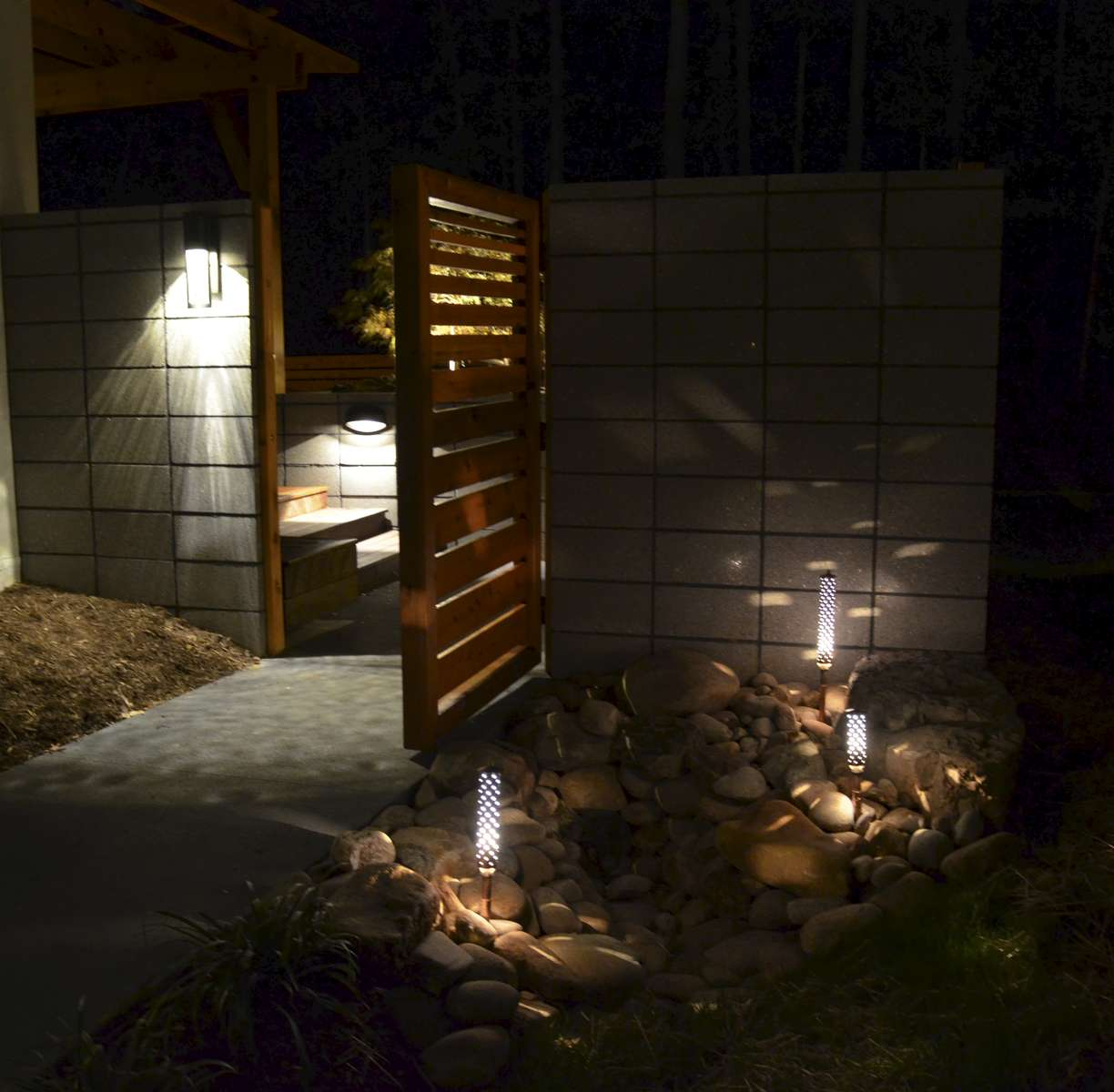 Entry into the backyard, as seen here in the evening, is accentuated by cedar privacy gates.