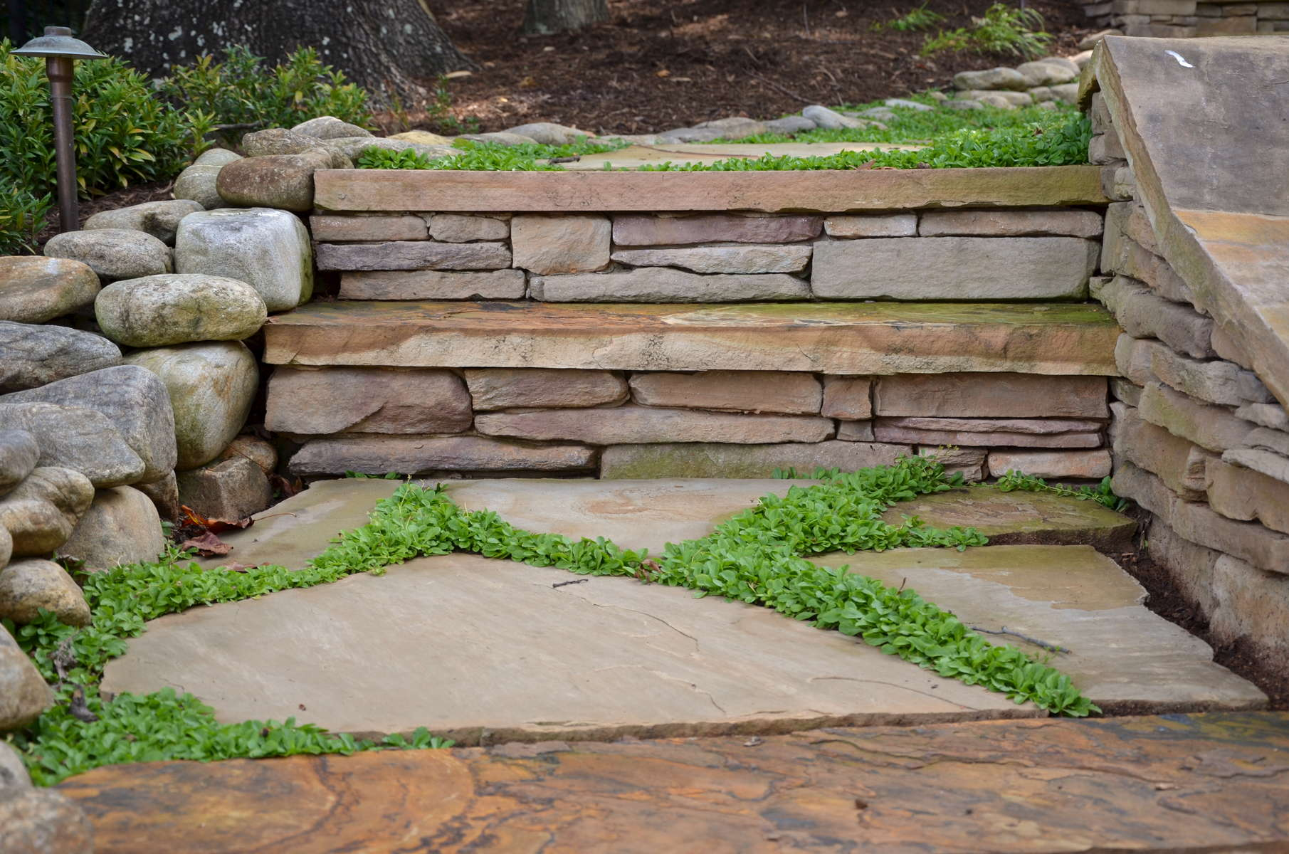 Stone naturally adheres both the site's aesthetics and utility in endleStone naturally adheres both the site's aesthetics and utility in endlessly appealing applications. Battered rubble stone stone walls protect original tree roots and serpentine stone dry creeks channel and diffuse storm water. Boulders edge paths, terminate walls and provide improvisational seating on a sunny afternoon.ssly appealing applications. Battered rubble stone stone walls protect original tree roots and serpentine stone dry creeks channel and diffuse storm water. Boulders edge paths, terminate walls and provide improvisational seating on a sunny afternoon.