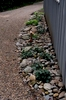 A freestanding garage located at the back entrance of the property is outfitted with river rock and perennials to help combat erosion and add character to an otherwise forgotten space.