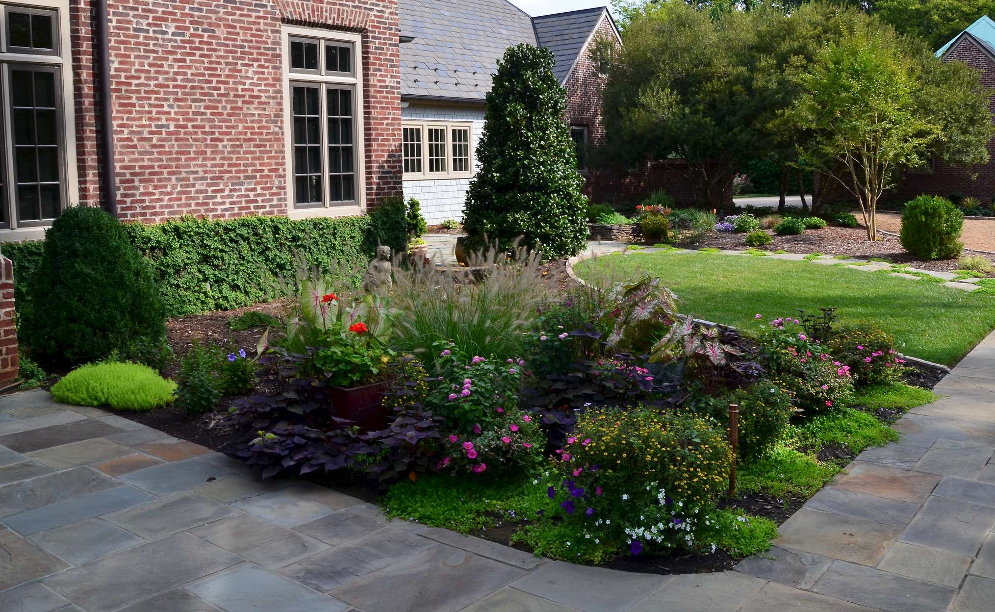 This area heralds the entrance to the main house. Complete with angelic-inspired statuary and adorned with a carefully planned container garden filled perennials, flowing vines and annuals such as geraniums, sweet potatoe vine, roses and decorative grasses.