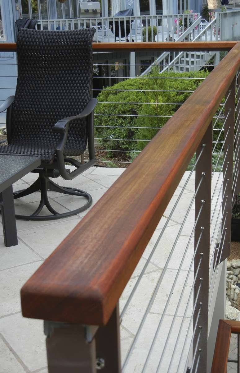 This detail view of the railing and Mahogany rail cap show the warm complimentary feel of the patio as it melds into the woodland landscape.