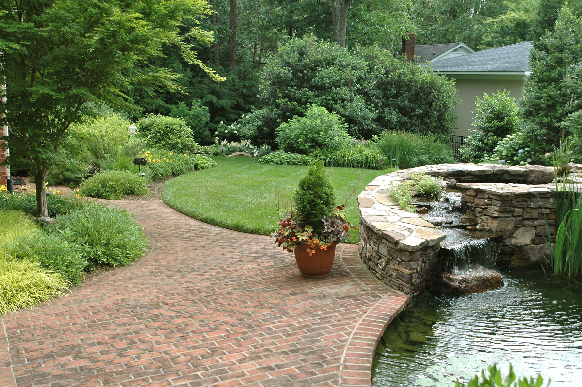 The bricked area adjacent to the water pond serves a dual purpose, as the seperation and connector to the driveway and garage as well as the lead into this lavish backyard.The custom water feature is designed to not only pool on top, but it also features a semi-circular spillway allowing the water to gently flow from the stones before entering the main pool below.
