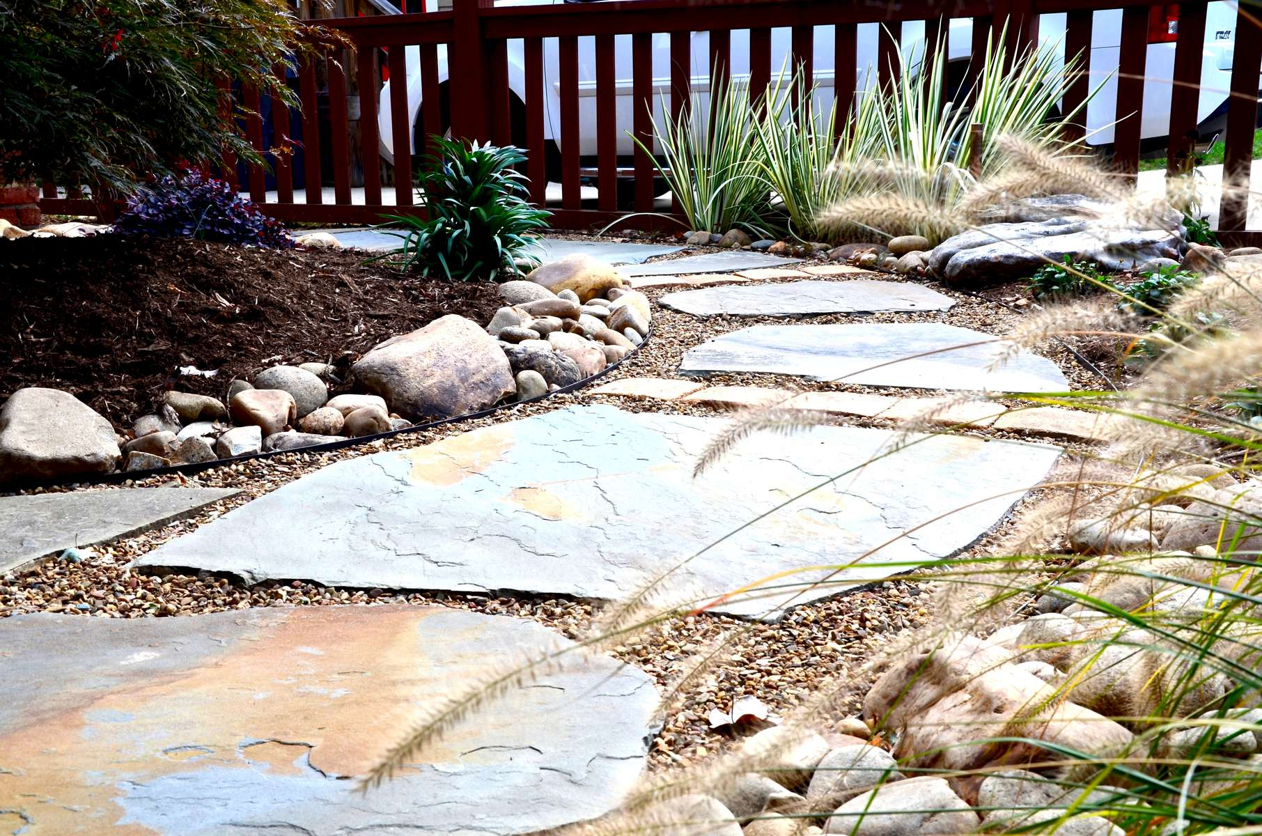 Compositions of smooth, cool river rock with boulders and over-sized natural stone paths with crushed stone infill commingle with expansive carpets of plush, colorful groundcovers in a rich, flowing ground plane.