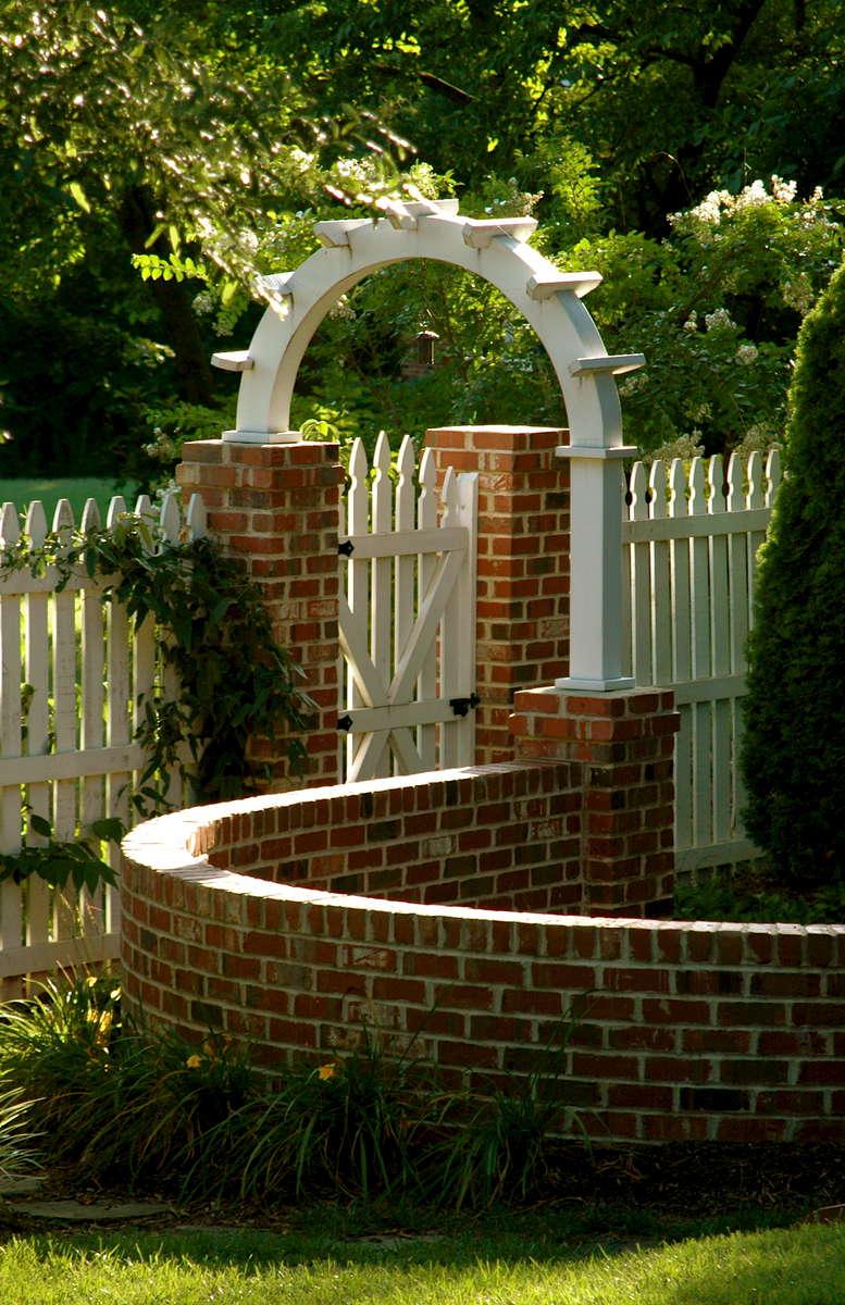 Serpentine brick wall establishes connecting garden rooms in this Williamsburg inspired garden