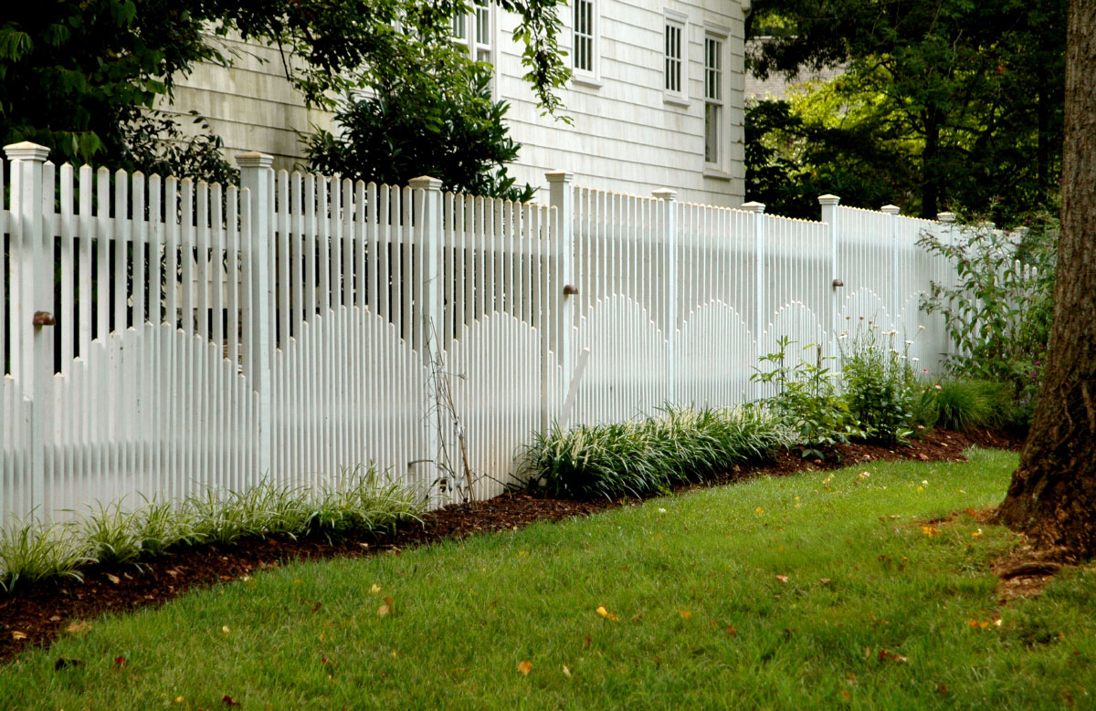 Along the southwest property line, a custom-designed semi-privacy fence sets the tone. Within each lower section, a repeating arched pattern rhythmically directs the eye toward the arbor entrance into an enclosed courtyard garden.