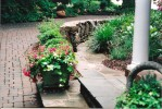 Elegant stonework and English-inspired perennials sweep you into the feeling of being in a formal English garden, right  in NC!