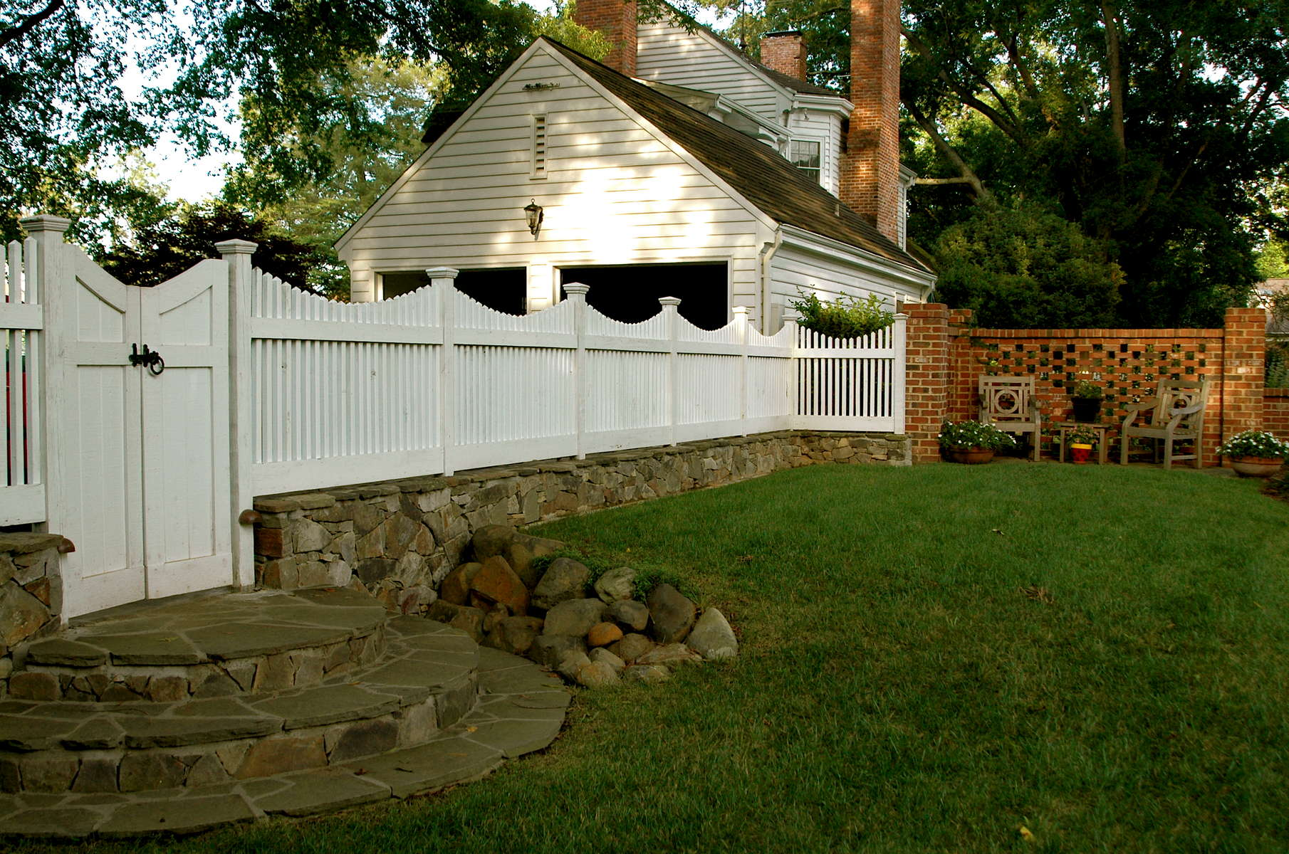 Traditional picket fence atop vintage stone knee wall