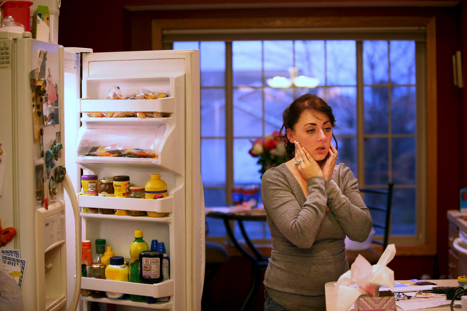 Jenny Muñoz pauses in her kitchen while preparing a meal for her daughters in St. Francis, Minn. With her husband serving overseas on his second tour with the National Guard, Muñoz often felt the stress of raising two daughters while working more than 50 hours a week.