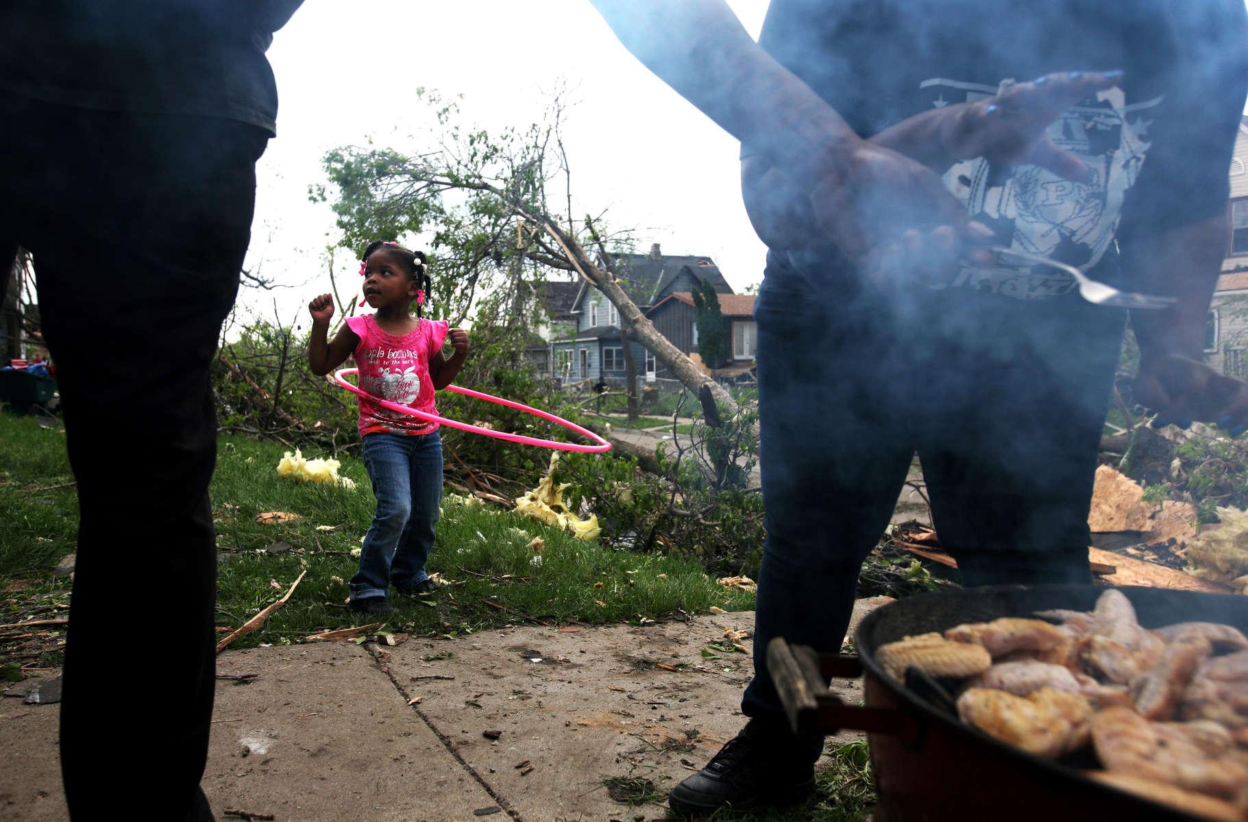 Following a devastating tornado, Laneik White, 4, plays with a hoola hoop as neighbors grill food for their community in Minneapolis, Minn.