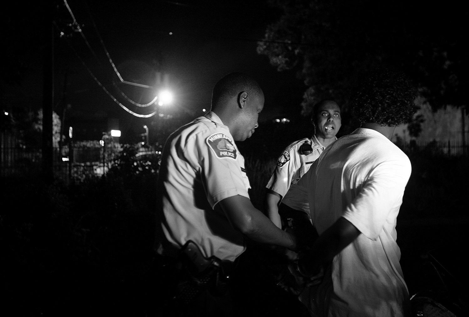 Officer Mohamed Abdullahi handcuffs a young offender as his partner Abdiwahab Ali assists in Minneapolis. Abdullahi and Ali were recruited by the Minneapolis Police Department to deter crime within the Somali-American population in the Cedar-Riverside neighborhood.