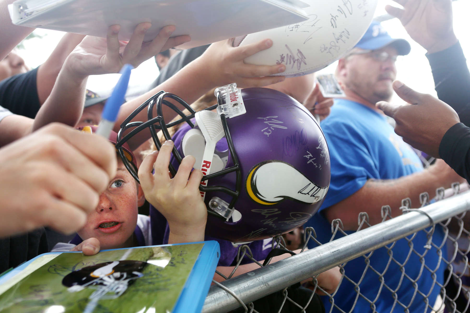 Bryant Brunz, 12, attempts to a get a helmet signed during the Vikings first day of training camp in Mankato, Minn.