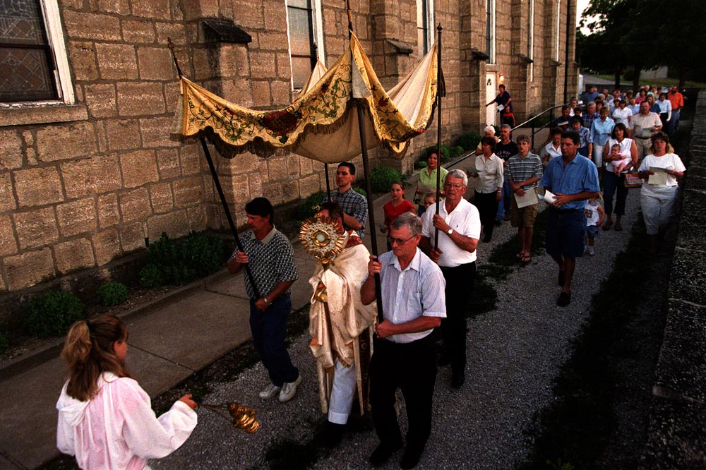 Members of Sacred Heart parish are led by Father Michael Murphy during the Corpus Christi procession. {quote}The great strength of this community is their cohesiveness, their willingness to live and worship together,{quote} Father Murphy said.
