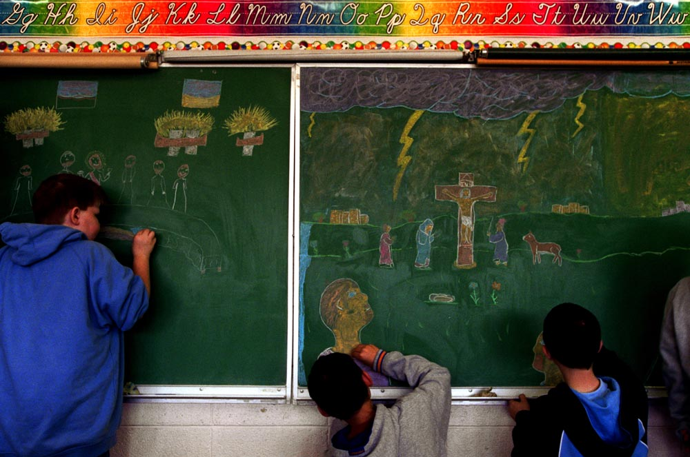 The fifth grade class works on an Easter mural during Holy Week at Sacred Heart School. Religion studies anchor the curriculum at the Sacred Heart, and most residents agree that, without the school, the community would not survive.