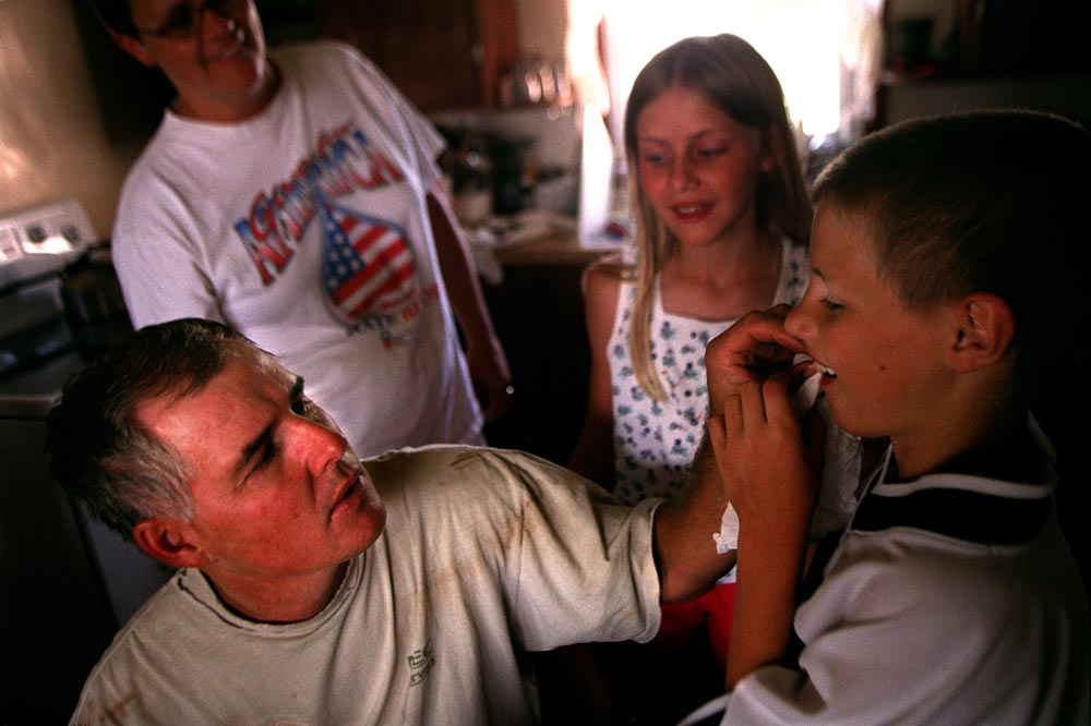 With his mother, Bert, and sister, Claire, encouraging him, John Fick leaves the fate of his loose tooth in the hands of his father Greg.